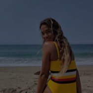 Woman on beach, wearing yellow swimsuit and looking over her shoulder