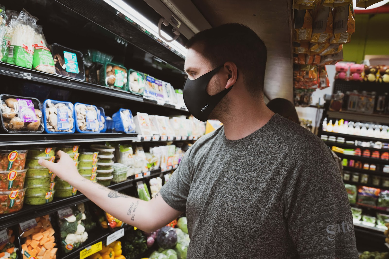 man shopping safely in mask