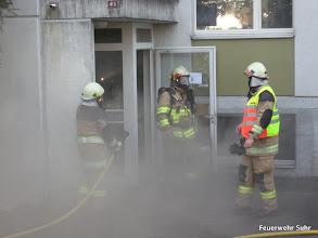 Photo: Ein Atemschutztrupp kommt aus dem Gebäude raus und informiert den Einsatzleiter (Warnweste).