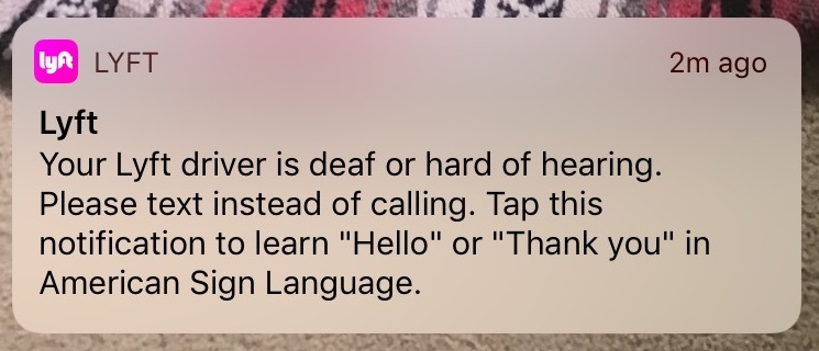 A push notification received by a Lyft passenger, telling her that her driver was deaf or hard of hearing, and that she should text them instead of call. The notification includes a link with instructions for communicating in American Sign language.