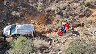 Los equipos de rescate atienden a la mujer junto al vehículo en el fondo del barranco.