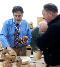 Photo: Stan Welborn discusses his bowl of balls that he turned from wood he had laying around the shop.