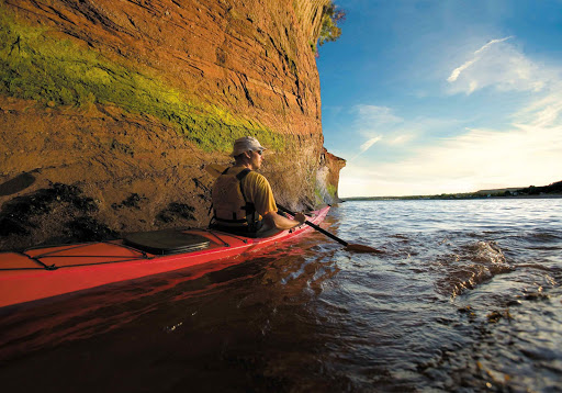 A kayaker pauses against a rock formation in the St. Martins Sea Caves in Saint John County, New Brunswick.