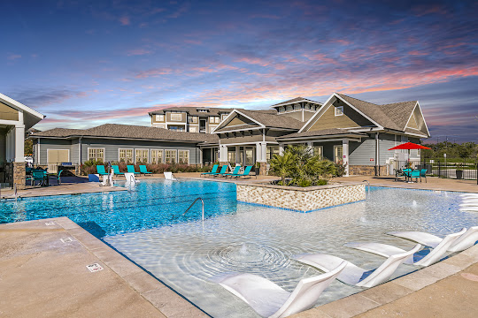 Overlook Exchange's resort-style swimming pool with lounge chairs at dusk