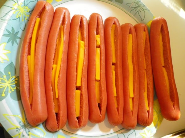 Slit wieners to within 1/2 inch od ends; insert 3 strips of cheese in...