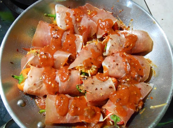 Add just a little sauce to bottom of baking dish.  Wrap prosciutto around...