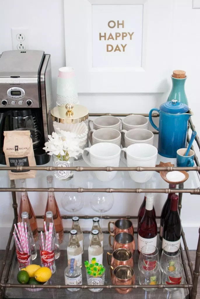 2 tier glass bar cart with coffeemaker and ingredients on top. Alcoholic beverages are stored on the bottom. Small golden sign sits above the cart on a white wall