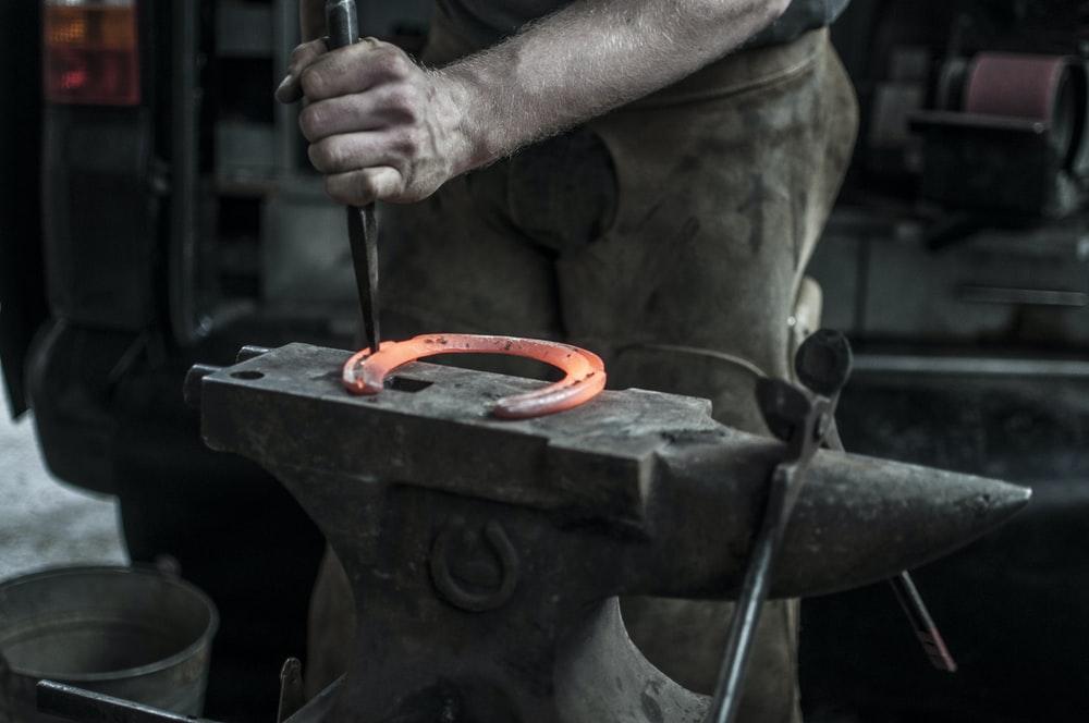 man forging horseshoe