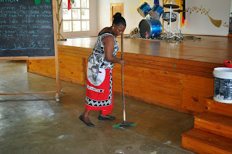Photo: Village woman cleaning the meeting place.