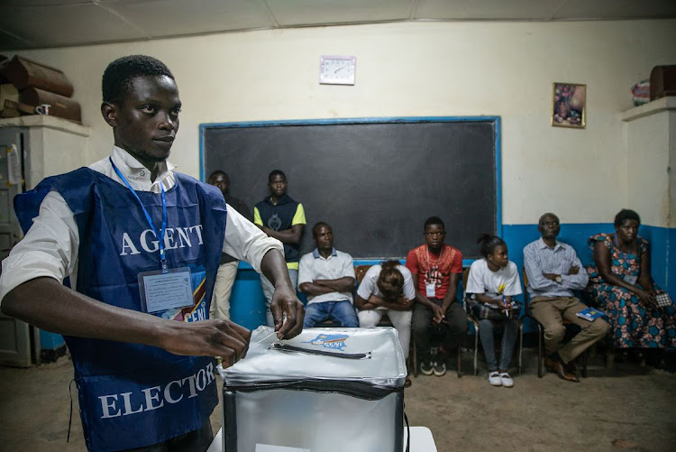 An Independent National Electoral Commission agent seals a ballot box in front of observers at the Kitendo voting centre in Lubumbashi's Mapala district on December 30, 2018. Picture: AFP/CAROLINE THIRION