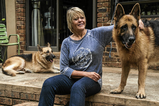 True blue: Glynnis Breytenbach with her Alsatians on her smallholding near Pretoria. In her book, she advises against 'believing you are the person your dog thinks you are'. Picture: WALDO SWIEGERS