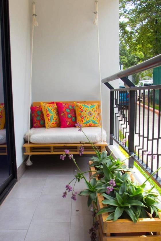 Varanda simples pequena com cadeira de balanço com estofado branco e almofadas coloridas e um vaso de plantas.