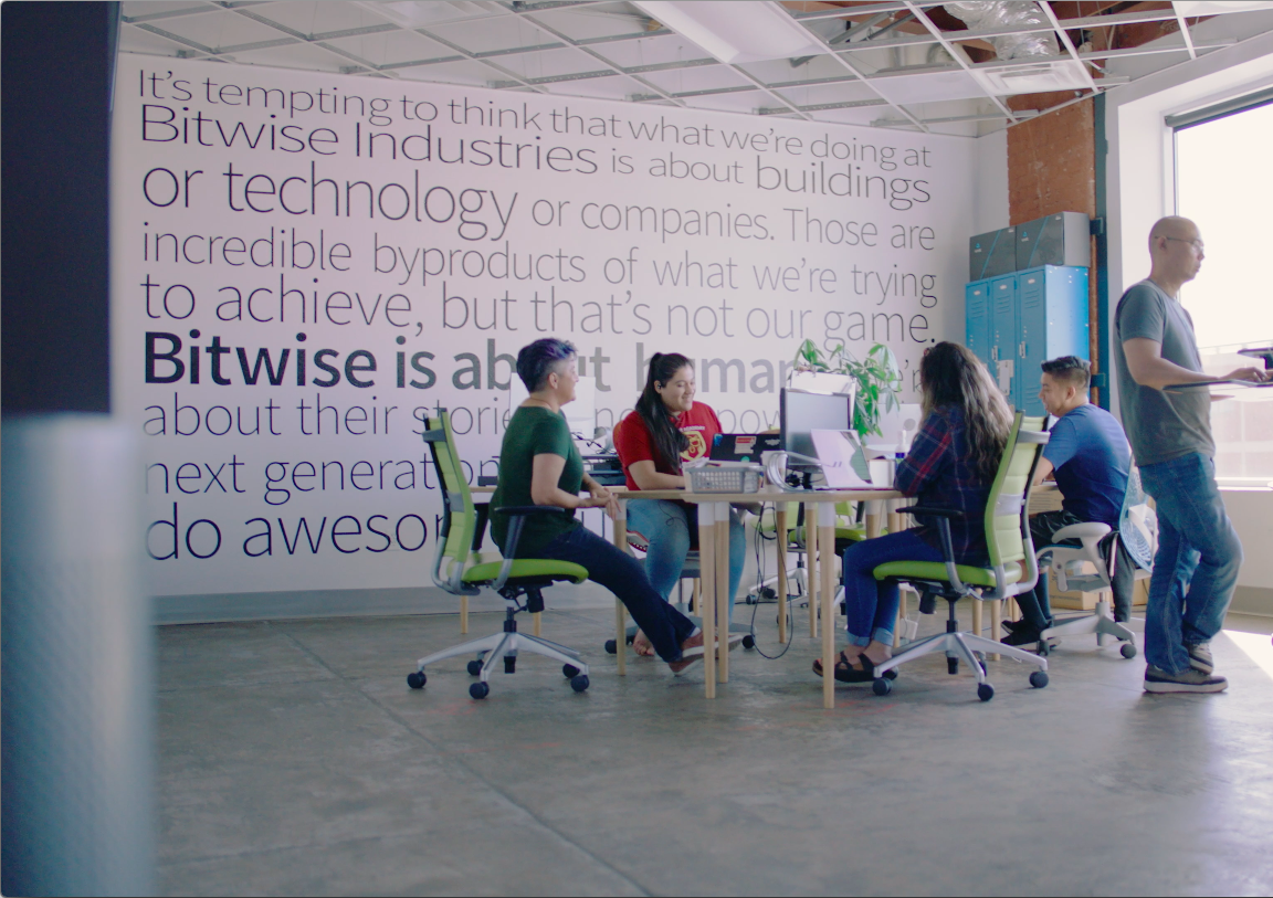 men and women sitting around table in office chairs talking inside of Bitwise office. man standing at laptop next to table.