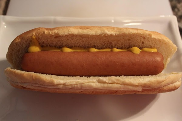 Place hot dog in a bun with a little mustard to taste