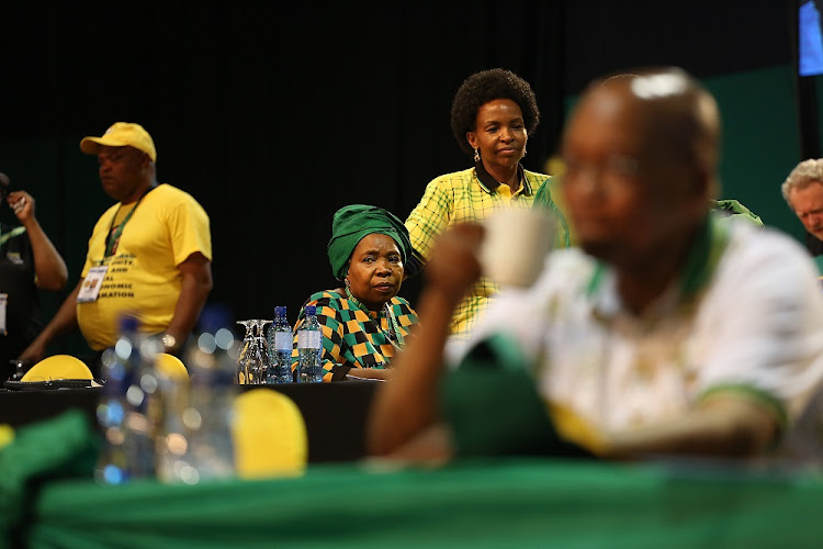 Nkosazana Dlamini-Zuma looks on in the background as the outgoing ANC President Jacob Zuma takes a sip from his cup at the 54th ANC Elective Conference at Nasrec, Johannesburg.