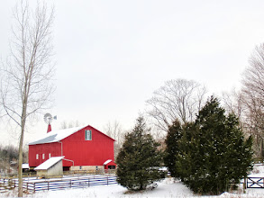 Photo: Red barn and windmill in the snow by pine trees and fences at Carriage Hill Metropark in Dayton, Ohio.