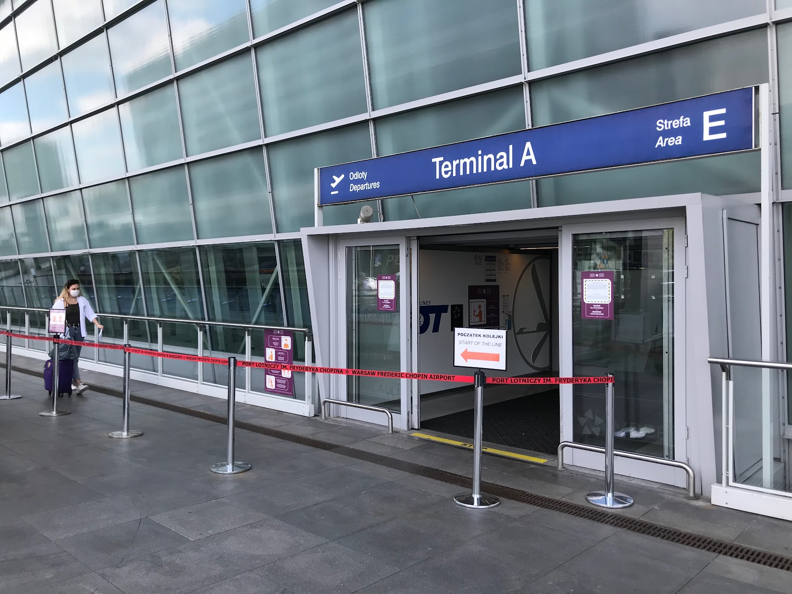 woman entering airport terminal at Warsaw Chopin Airport in June 2020. Most of the entrances are closed, temperature checks for passengers and mandatory masks. COVID-19 changed airplane travel.
