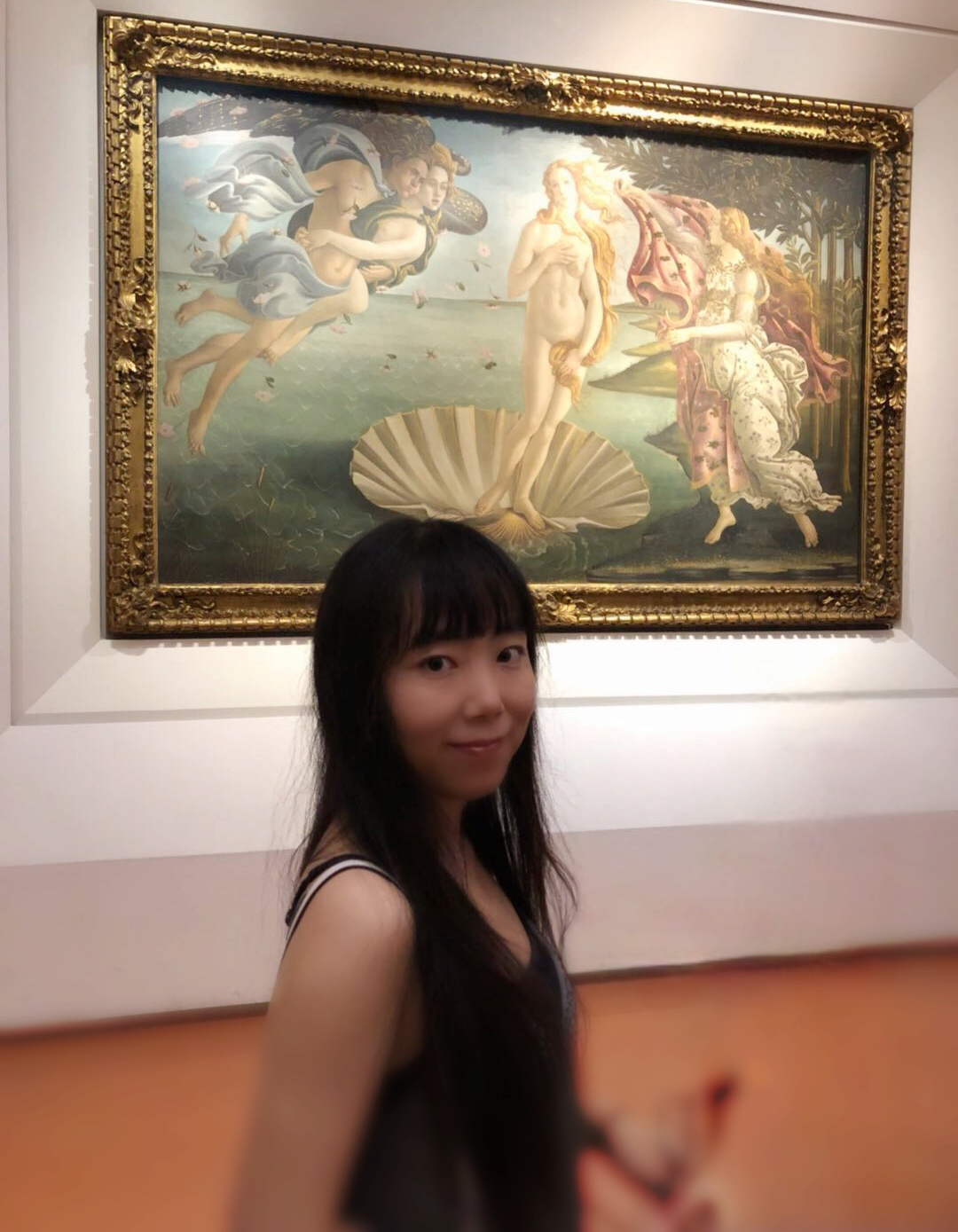 a woman is smiling in front of a painting