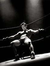 Photo: John Payne got the full sex symbol treatment by lighting his body with a single high, bright lamp.  Note that his face is softly lit, as if the focus is meant to be on the body.  The frank sexuality of this publicity shot (promoting a film in which he plays a boxer) is rather extraordinary. One has to ask oneself how the visual codes both promote and deny the sexuality--e.g., by aestheticizing the body through lighting.