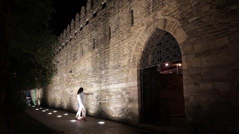 Vor der Stadtmauer von Baku machen zwei junge Frauen ein Selfie.