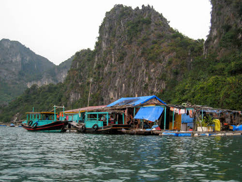 Passing by fishing village while kayaking in Halong Bay