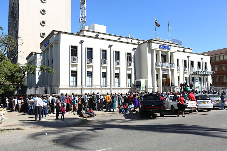 Customers wait in a long queue outside a bank in central Harare, Zimbabwe, on Saturday. Picture: EPA/AARON UFUMELI