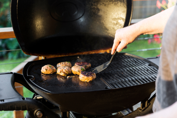 Grilling burgers on a flat outdoor griddle surface