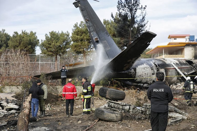 Firefighters and security forces gather amidst the debris of a Boeing 707 cargo plane that reportedly crashed into a residential complex near the Iranian capital Tehran with 10 people onboard on January 14 2019.