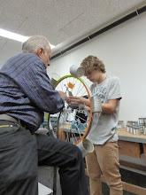 Photo: Lehrer Peter Gehrer hilft beim festdrahten der plasmageschnittenen Teile