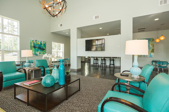 Clubhouse seating area with four blue chairs, mounted TV, and coffee table