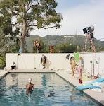 zwembad bij Hollywood met naakte vrouw in water met een masker, naakte vrouw in gesprek met andere vrouw, man in rijkleding nonchalant rondkijkend en nog 2 figuranten