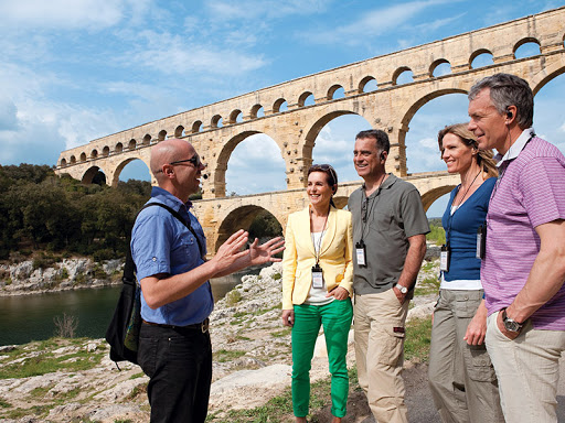 uniworld-south-france.jpg - A tour guide tells visitors the history of Pont du Gard, an ancient Roman aqueduct bridge in southern France.