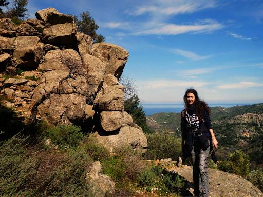 Voutsides Ikaria winter falls 25: Γλυπτοί βράχοι, κορίτσι στα σκούρα, ορίζοντας μπλε