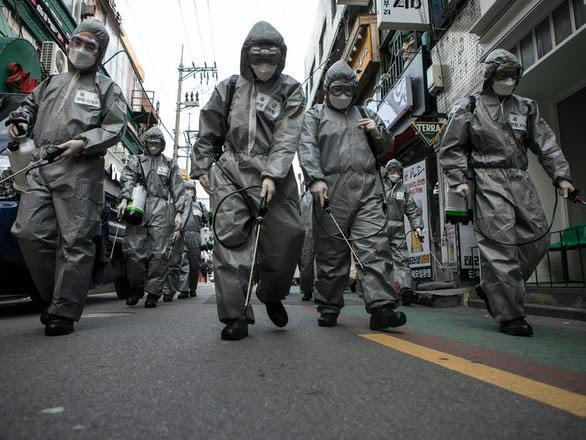 Các thành viên quân đội Hàn Quốc khử trùng đường phố Seoul khi COVID-19 lây lan mạnh ở nước này