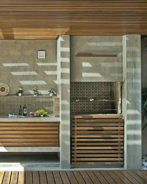 Area gourmet com cimento queimado revestindo paredes e churrasqueira, deck de madeira no chão, madeira ripada no teto, e detalhes de madeira na pia e churrasqueira.