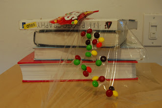 Photo: Requirement 4 (levitation): the set-up for tumbling Skittles. I taped a bunch (maybe too many) of Skittles onto plastic wrap and draped it off the books onto the table. Then, I proceeded to very very carefully erase the background and stack the photos as accurately as possible.