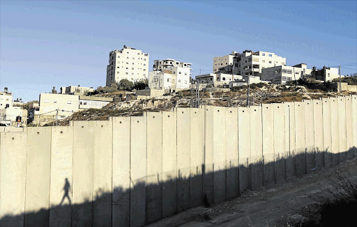 The Shuafat refugee camp behind a section of the controversial Israeli barrier in the West Bank. Israeli and Palestinian negotiators this week met at the negotiating table for the first time in three years