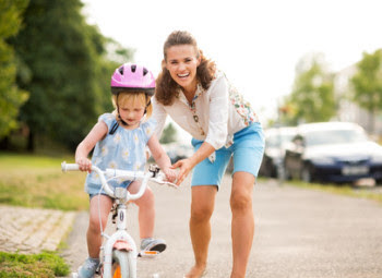 Mother helping her little girl learn to ride a bike