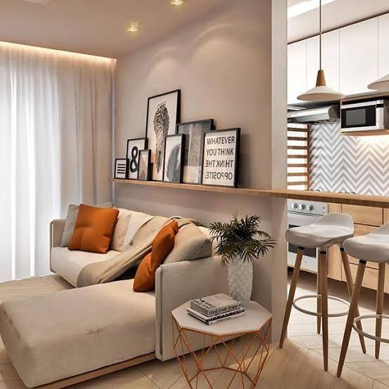 Sala com sofá cinza claro e almofadas caramelo, mesa de canto e bancada que serve como prateleira na sala de estar e bancada na cozinha.