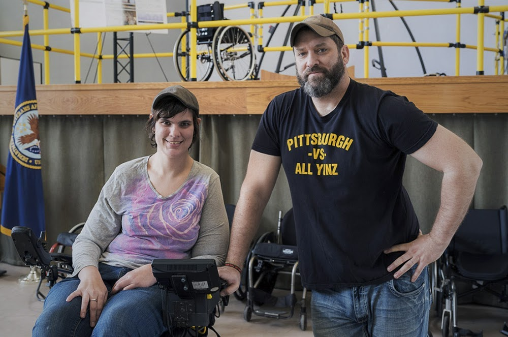 A person in a wheelchair next to a person standing with their hand resting on the arm of the wheelchair.