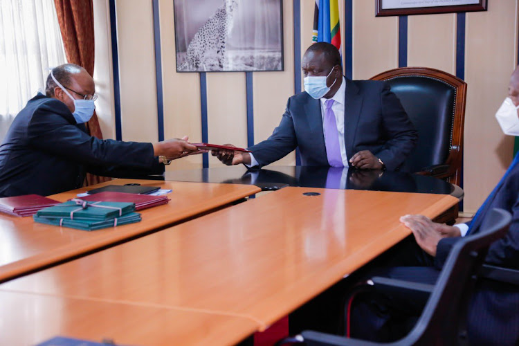 Interior CS Fred Matiang'i receives the report from Inter Faith Council Chairperson Rev. Anthony Muheria on Monday July 6, 2020.