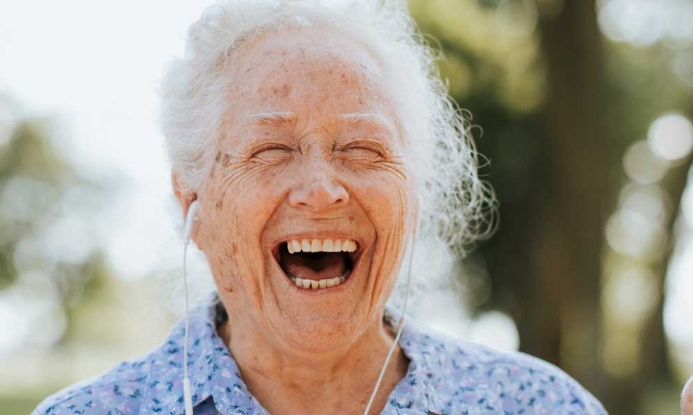 Older Woman Listening to Music and Laughing