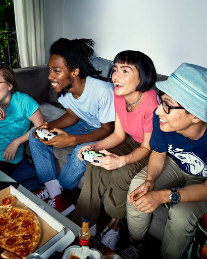 Young people on a couch smile at the TV as they game with their Stadia controllers.
