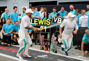 Mercedes' Formula One world champions driver Lewis Hamilton celebrates winning the race with teammate Valtteri Bottas, who finished third, and the Mercedes team during the Italian Grand Prix at Circuit of Monza on September 2, 2018.