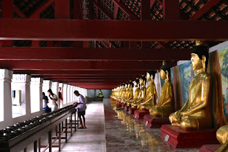 Photo: Buddha images line the gallery surrounding the temple. Here, a worshipper engages in the ritual of dropping coins into 108 monk's alms bowls – symbolic of donating sustenance to support the order of monks in the temple.