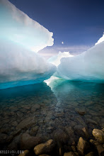 Photo: Glowing sea ice Ellesmere island, Canadian Arctic From the photo of the day at http://ww.kylefoto.com  The sea ice in the arctic is usually quite featureless, but after a while it piles up on top of itself into large conglomerates. The tides are still prevalent in the arctic and can ground the sea ice by the shore, revealing interesting features that would normally be underwater. I waited until the kittiwake that was flapping around above me was in the patch of sky exposed, just to give the photo an extra element.  Photographic details: Back lighting situations are usually thought of as a disadvantage by photographic enthusiasts, but I have found that more difficult situations provide unique opportunities. Instead of just lighting the surface of the ice, now the light is travelling through it, making it glow! Walking through this little cavern of abandoned sea ice felt like having my own personal fantasy land, as I knew in a short time the tide would come and take it all away, never to be seen exactly like this again.  1/50s f/4.5 ISO50 16mm