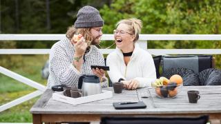 un hombre y una mujer sentados al aire libre riéndose