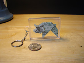 Photo: Model: Money Pig;  In a plastic box with a chain and keyring attached;  Creator: Paul Jackson;  Folder: William Sattler;  1 dollar;  Publication: Practical Origami (Rick Beech) ISBN 1-84309-392-8