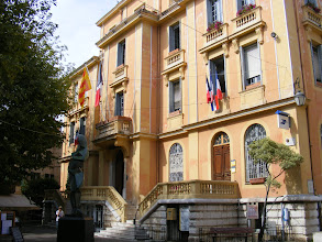 Photo: The ochre-colored City Hall on Place Clemenceau is celebrating its 100th birthday. We assume that the red and yellow flag next to the French red-white-and-blue Tricolore is the Departmental (Alpes-Maritimes) one. We also usually see the white-stars-on-blue European Union flag, but none is apparent here.