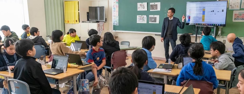 児童生徒のいる教室で先生がモニターを指す